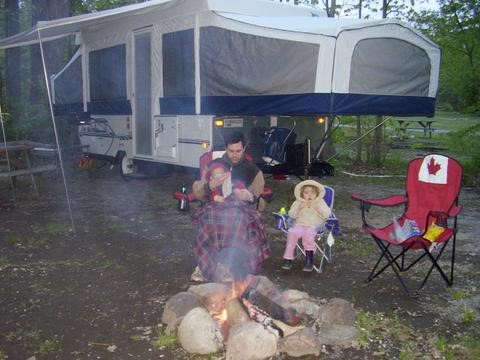 eating around a camp fire with a motorhome in the background